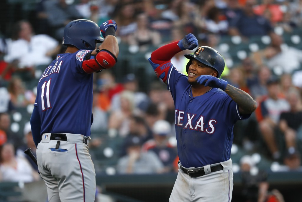 Texas Rangers' Willie Calhoun, right, celebrates his solo home run with Ronald Guzman in the fifth inning of a baseball game against the Detroit Tiger...