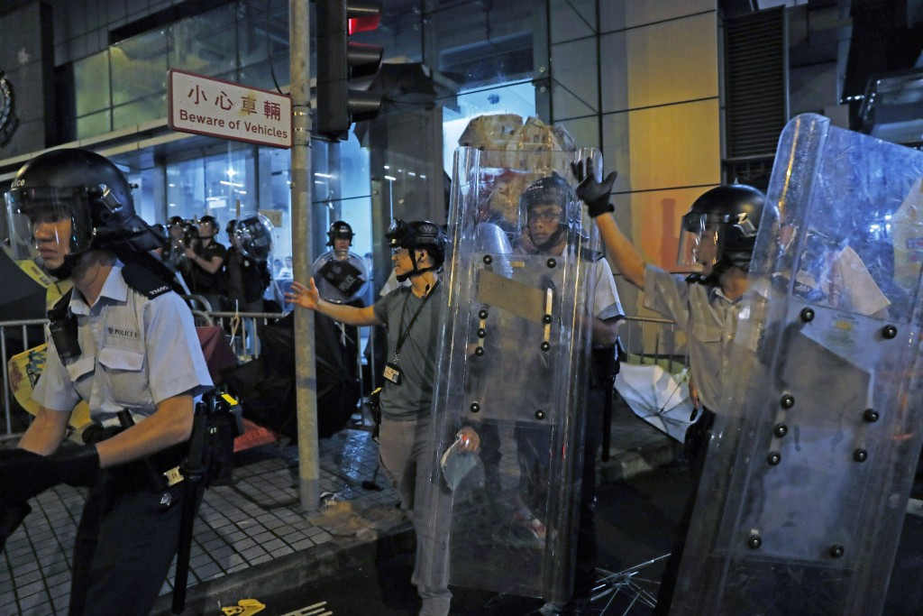 Riot police walk over barricades blocked by protesters outside the police headquarters as thousands gathered to demand for an independent inquiry into...