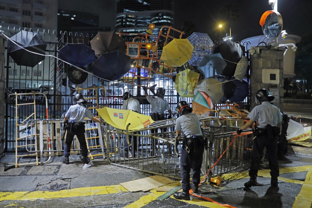 In this Thursday, June 27, 2019, file photo, riot police clear barricades blocked by protesters outside the police headquarters as thousands gathered ...