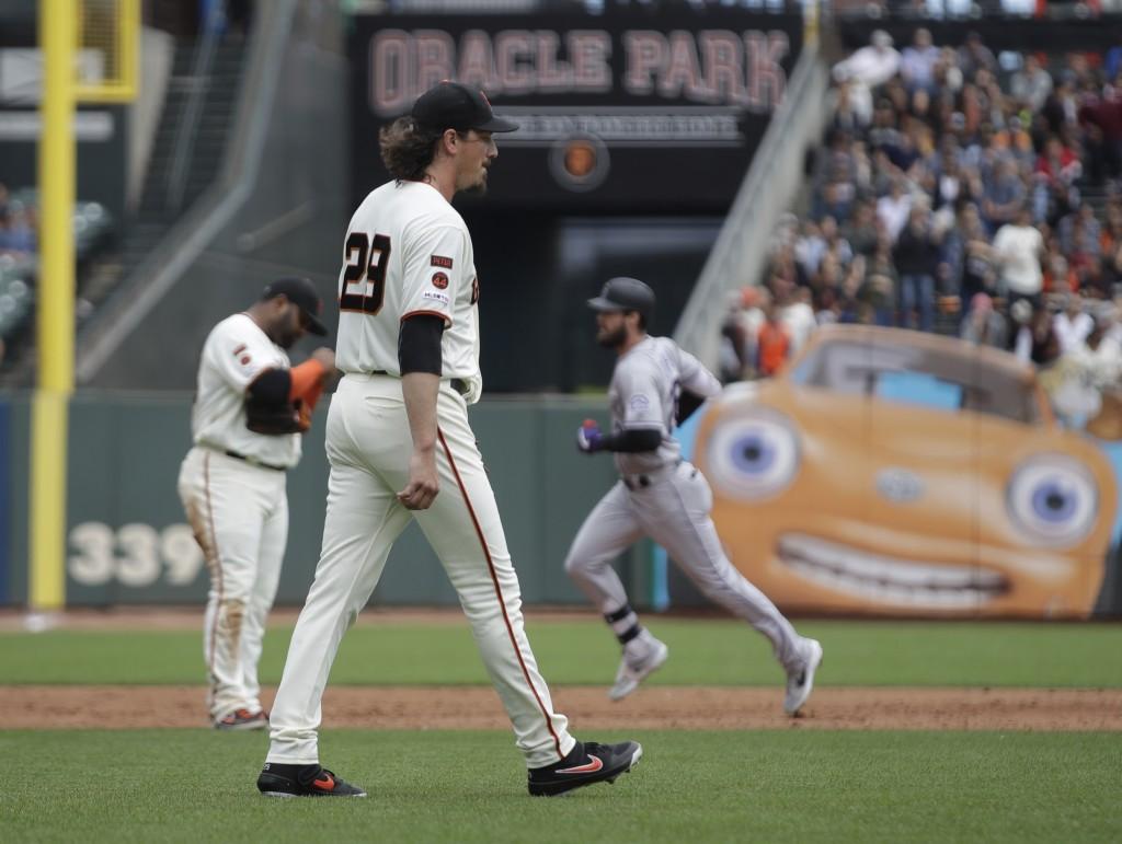 San Francisco Giants' Jeff Samardzija (29) walks back to the mound as Colorado Rockies' David Dahl, right, runs the bases after hitting a grand slam i...