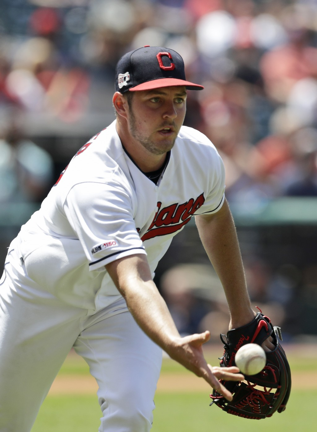 Cleveland Indians starting pitcher Trevor Bauer tosses the ball to first base to get Kansas City Royals' Whit Merrifield out in the fifth inning in a ...