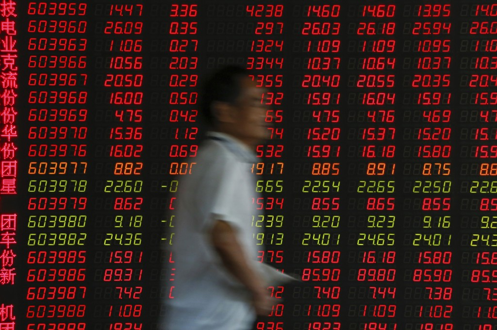 An investor walks by an electronic board displaying stock prices at a brokerage house in Beijing, Thursday, June 27, 2019. Asian stocks advanced Thurs...