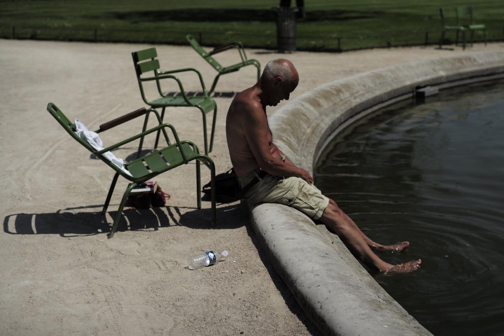A man puts his feet in a fountain Thursday, June 27, 2019 in the Tuileries gardens in Paris. Around France, some schools are closed because of high te...