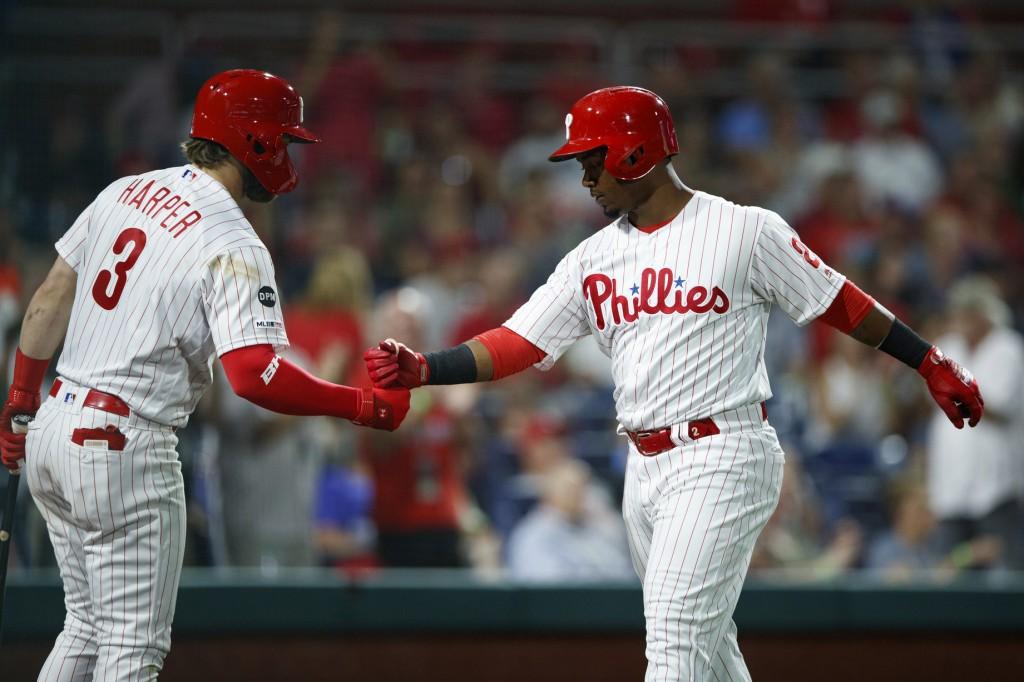 Philadelphia Phillies' Jean Segura, right, and Bryce Harper celebrate after Segura's home run off New York Mets starting pitcher Jason Vargas during t...