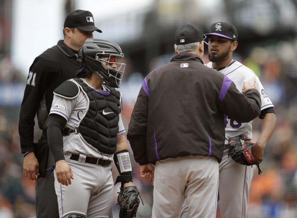 Colorado Rockies pitcher German Marquez, right, listens to manager Bud Black, second from right, in the first inning of a baseball game against the Sa...