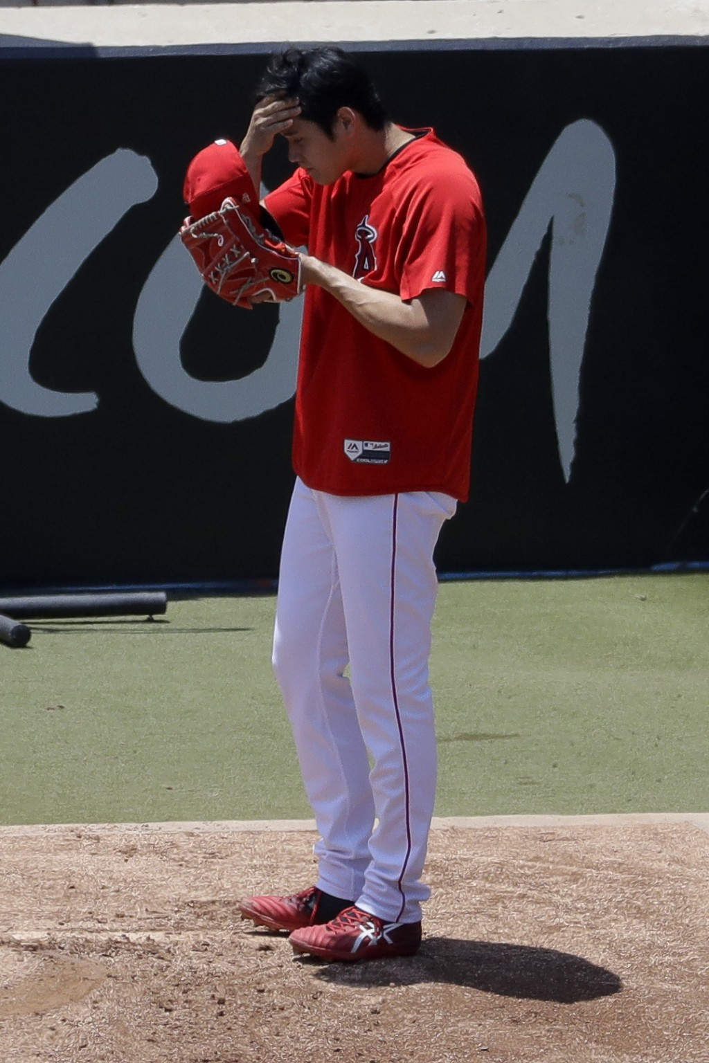 Los Angeles Angels' Shohei Ohtani wipes his face after throwing in the bullpen before a baseball game against the Cincinnati Reds in Anaheim, Calif., ...
