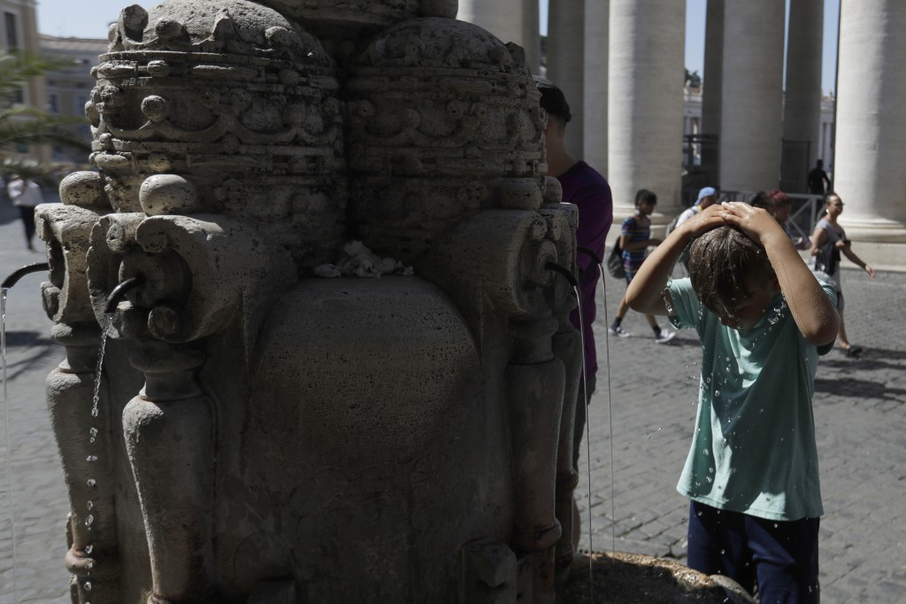 A child cools off at a fountain near St. Peter's Square at the Vatican, Thursday, June 27, 2019. The Civil Protection service in Rome also planned to ...