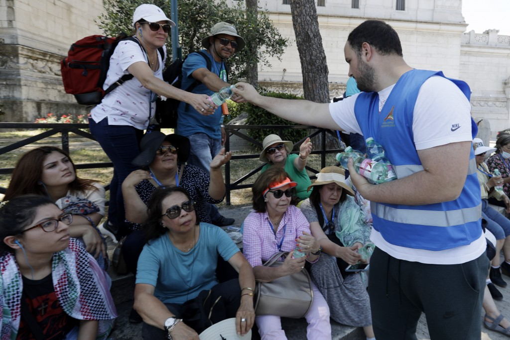 A Civil Protection volunteer delivers free bottles of water to tourists in Rome, Thursday, June 27, 2019. The Civil Protection service in Rome planned...