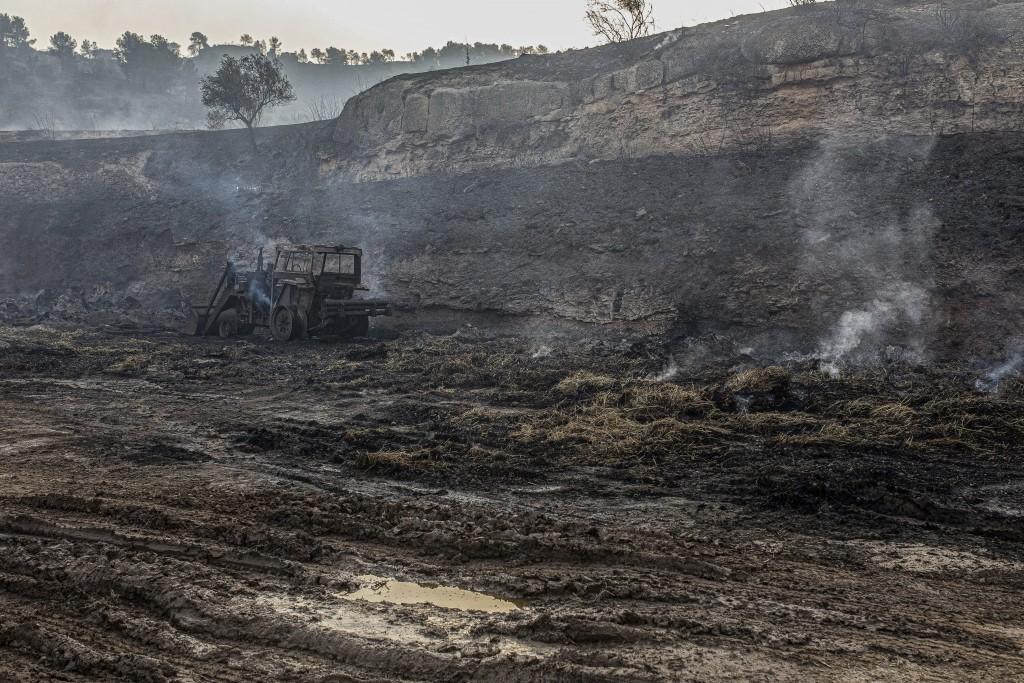 Smoke rises from the burned landscape after a wildfire in Torre de l'Espanyol, near Tarragona, Spain, Thursday, June 27, 2019.  The Catalonia region o...