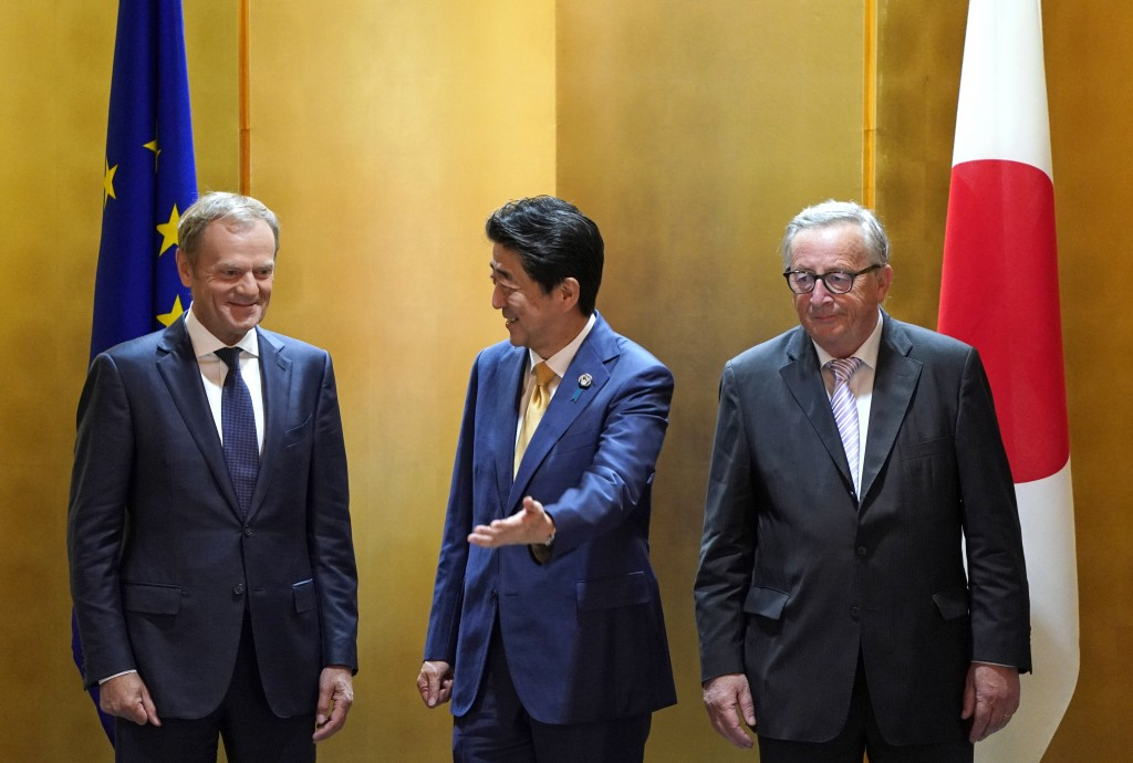 European Commission President Jean-Claude Juncker, right, and European Council President Donald Tusk, left, are escorted by Japanese Prime Minister Sh...
