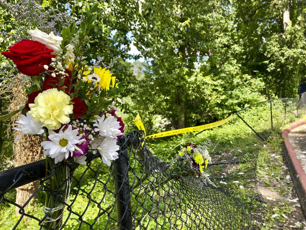 Bouquets of flowers sit on a fence on Wednesday, June 26, 2019, that was knocked down when a driver crashed into a swimming hole in Washougal, Wash., ...