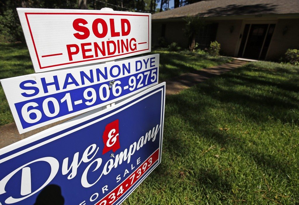 """In this June 13, 2019, photo a house on the market has a """"sold pending"""" sign fixed on the realtor's sign in northeast Jackson, Miss. On Thursday, June..."""