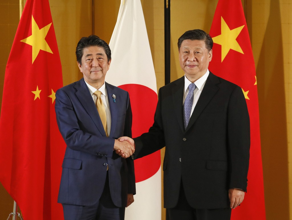 Chinese President Xi Jinping, right, and Japanese Prime Minister Shinzo Abe shake hands at the start of their talks at a hotel in Osaka, western Japan...