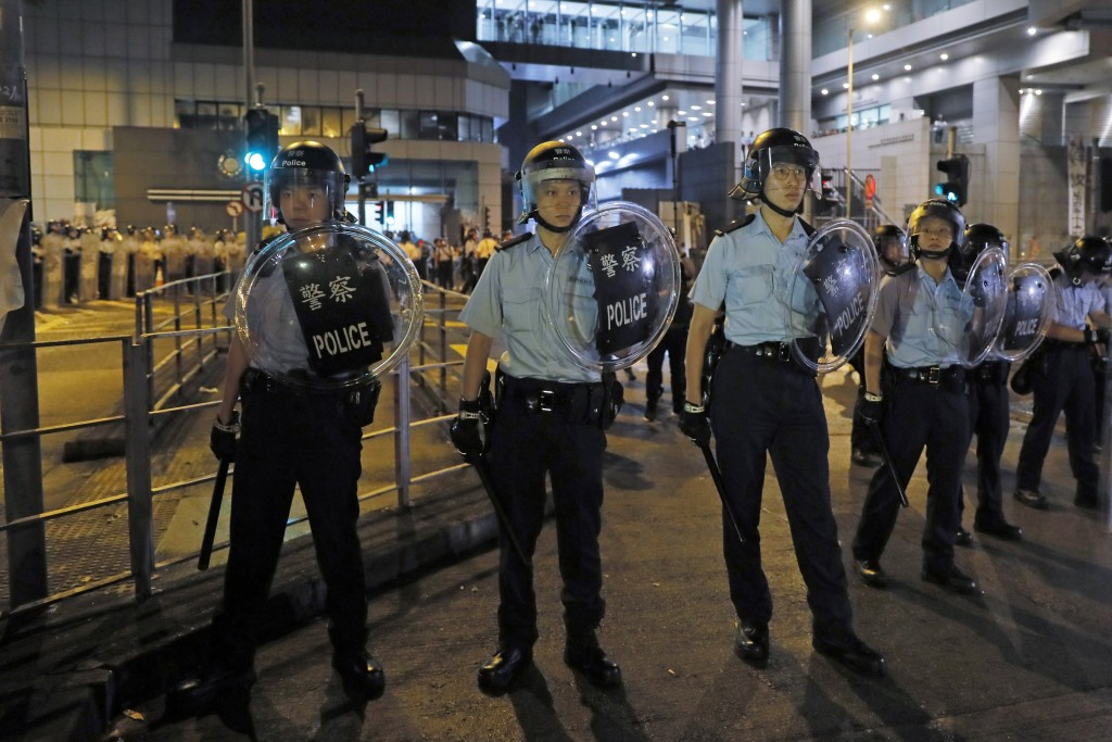 Riot police stand guard outside the police headquarters as thousands gathered to demand for an independent inquiry into a heavy-handed police crackdow...
