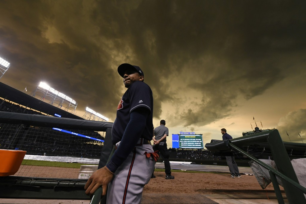 Atlanta Braves left fielder Johan Camargo looks on from the dugout during a lightning delay in the fourth inning of the team's baseball game against t...