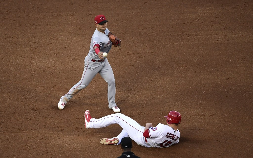 Los Angeles Angels' Dustin Garneau, right, is forced out at second as Cincinnati Reds shortstop Jose Iglesias throws out Tommy La Stella at first duri...