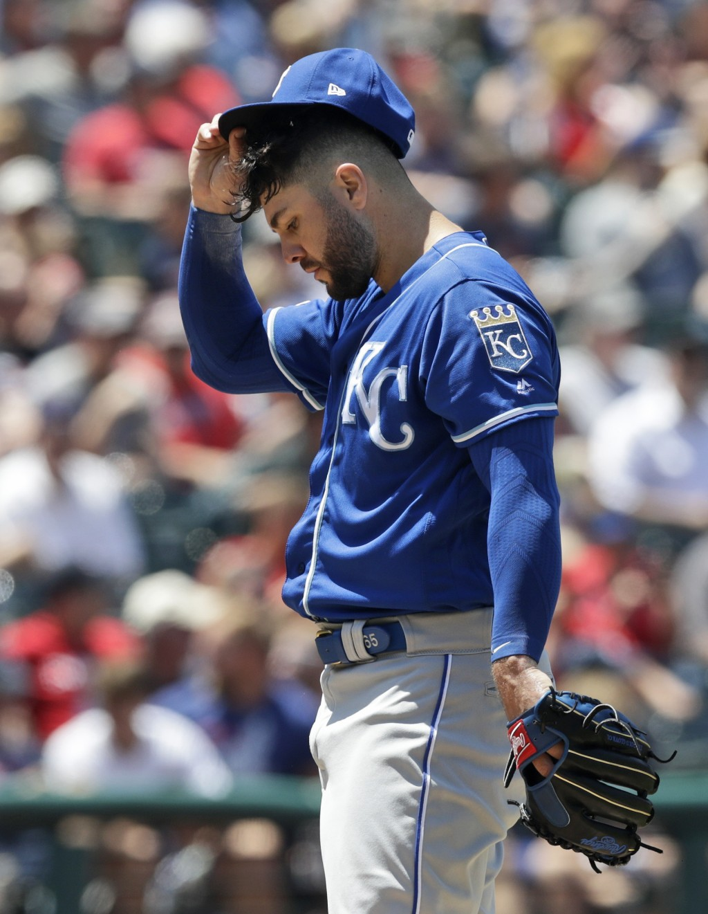 Kansas City Royals starting pitcher Jakob Junis adjusts his cap in the fourth inning in a baseball game against the Cleveland Indians, Wednesday, June...