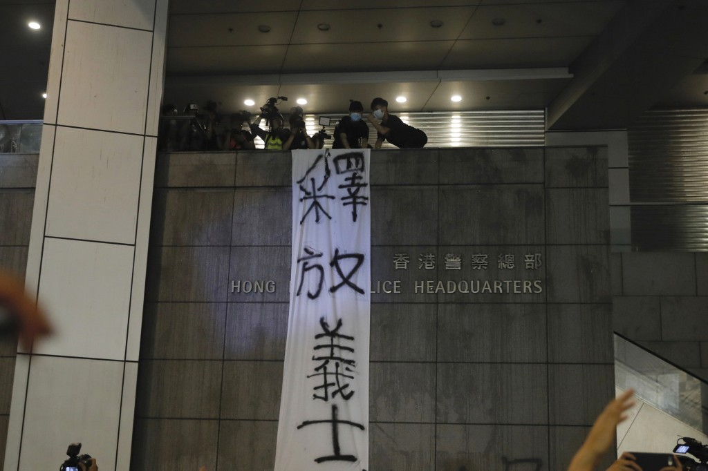 "Protesters hang a banner that reads: ""Free the righteous"" outside the police headquarters as they demand for an independent inquiry into a heavy-hande..."