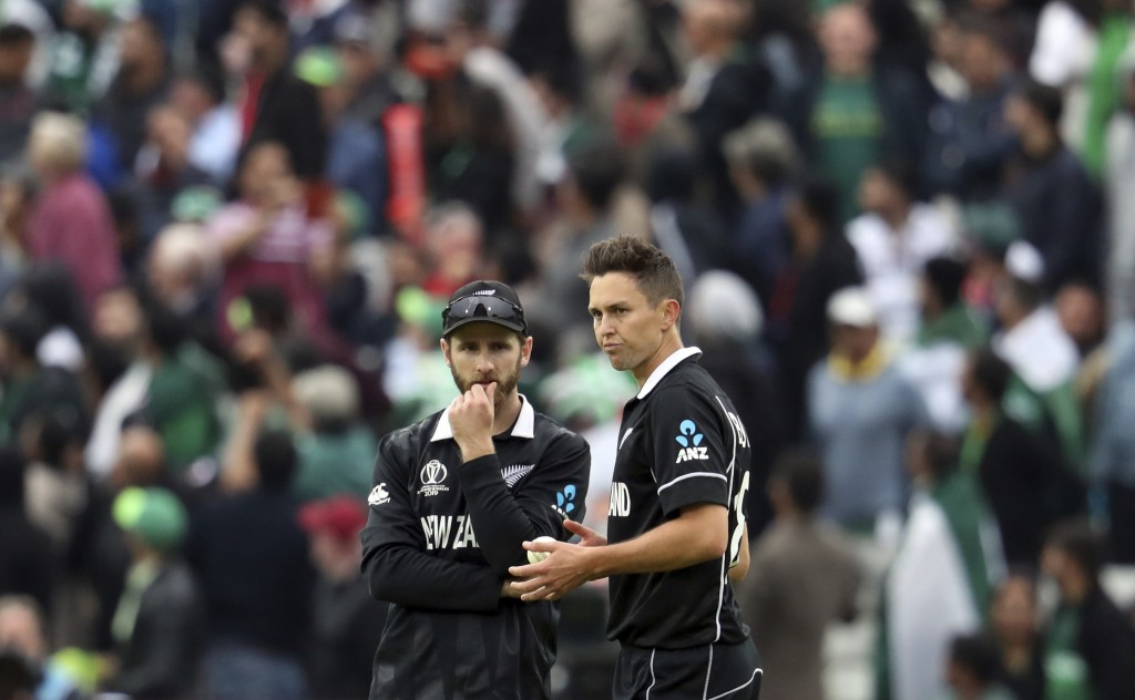 New Zealand's captain Kane Williamson, left, discusses with bowler Trent Boult, middle, during the Cricket World Cup match between New Zealand and Pak...