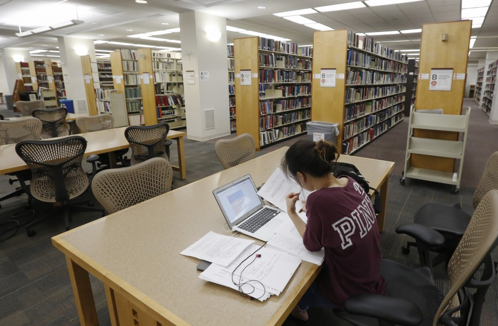 In this June 20, 2019, photo a student works in the library at Virginia Commonwealth University in Richmond, Va. Those who graduate college with stude...