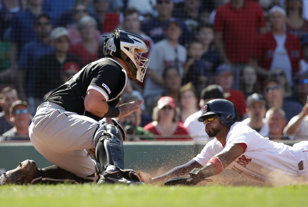 Boston Red Sox's Eduardo Nunez slides safely into home to score on a fielder's choice grounder by Mookie Betts as Chicago White Sox catcher James McCa...