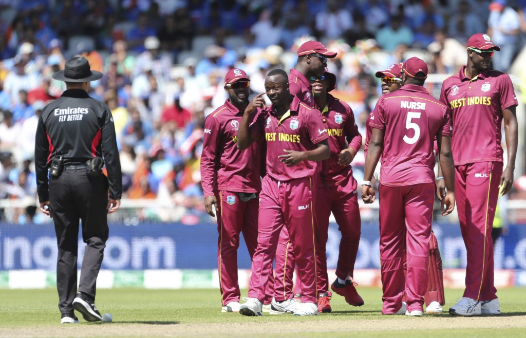 West Indies' Kemar Roach, third left, gestures to the umpire, left, after asking for a successful review for the wicket of India's Kedar Jadhav during...