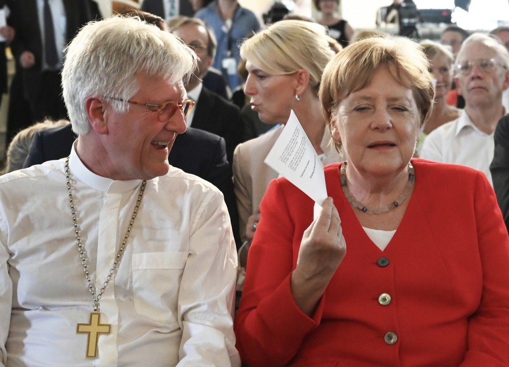 German Chancellor Angela Merkel fans herself with a piece of paper to cool down as she sits next to Heinrich Bedford-Strohm, Council President of the ...