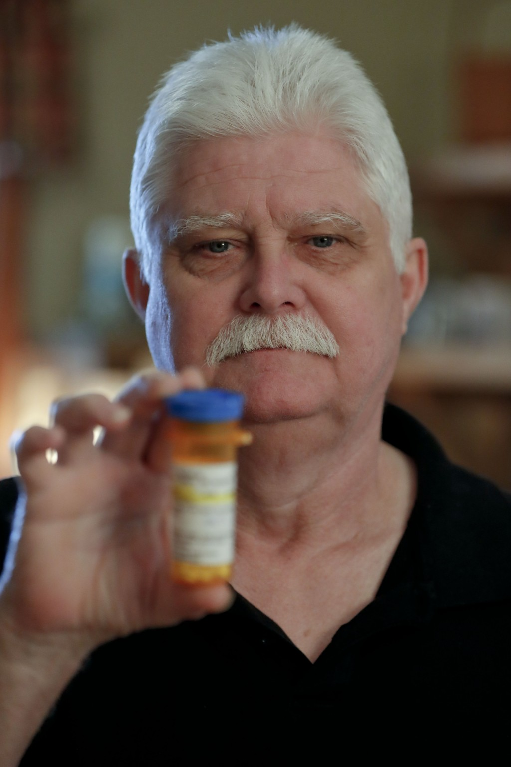 In this April 8, 2019, photo at his home in Derry, Pa., Chuck Pope shows the only medication he uses now to alleviate his rheumatoid arthritis conditi...