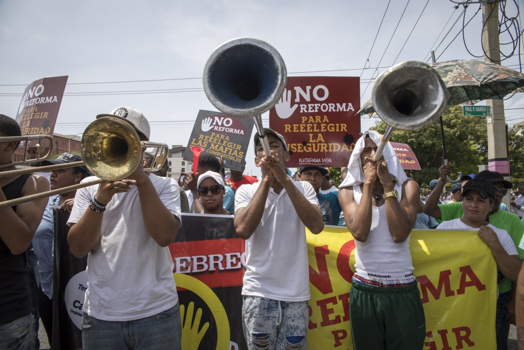 People gather outside the National Congress during a protest against a Constitutional reform that would allow President Danilo Medina a third term in ...