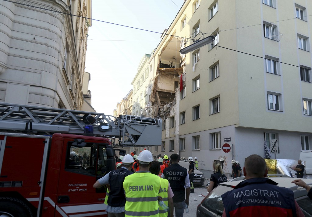 Firefighters search through the rubble of a exploded building in Vienna, Austria, Wednesday, June 26, 2019. A suspected gas explosion blew a gaping ho...