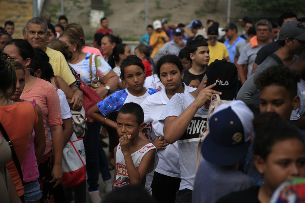Migrants from countries including Honduras, Cuba, Venezuela, and Nicaragua, line up to receive a meal donated by volunteers from the U.S., at the foot...