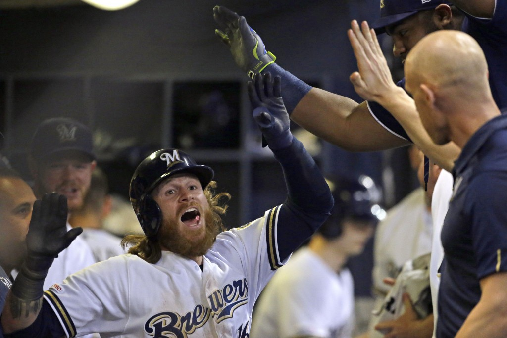 Milwaukee Brewers' Ben Gamel is congratulated in the dugout after hitting an inside-the-park home run during the sixth inning of the team's baseball g...