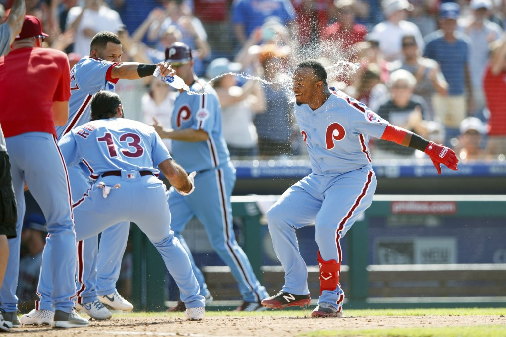 Philadelphia Phillies' Jean Segura, right, celebrates with teammates after hitting a game-winning three-run home run off New York Mets relief pitcher ...