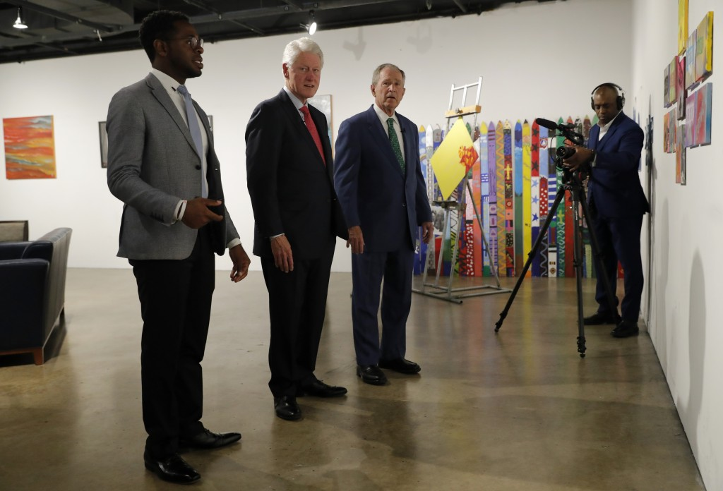 Byron Sanders, left, President and CEO of Big Thought, shows former Presidents Bill Clinton, and George W. Bush, art created by some of the staff and ...