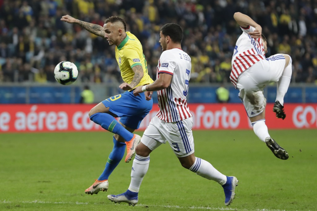 Brazil's Everton, left, vies for the ball with Paraguay's Juan Escobar, center, during a Copa America quarterfinal soccer match at the Arena do Gremio...