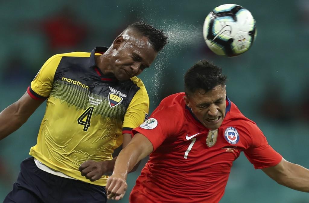 Ecuador's Pedro Velasco, left, and Chile's Alexis Sanchez, go for a header during a Copa America Group C soccer match at the Arena Fonte Nova in Salva...