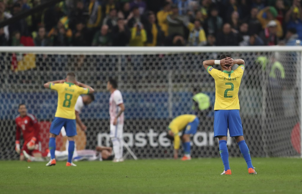 Brazil's soccer players react during a Copa America quarterfinal soccer match against Paraguay at the Arena do Gremio in Porto Alegre, Brazil, Thursda...