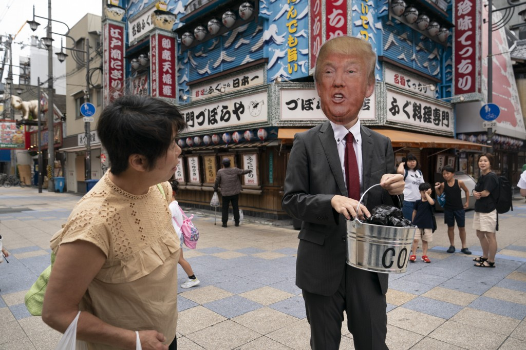 In this Friday, June 28, 2019, file photo, a Japanese woman looks at an environmental activist wearing a mask depicting U.S. President Donald Trump du...