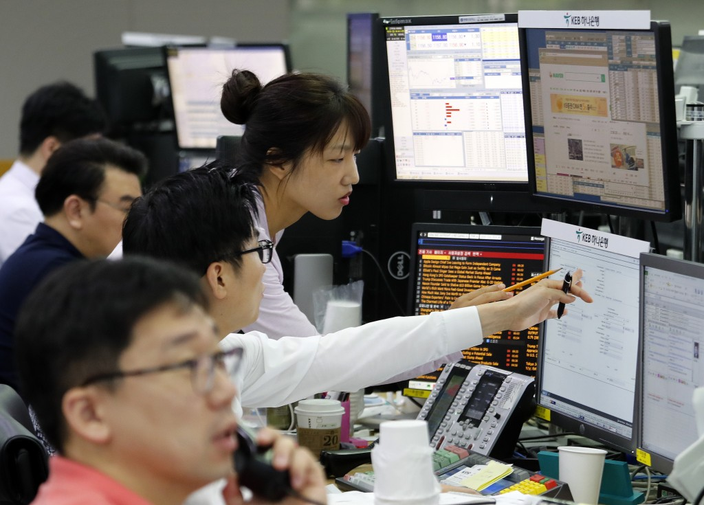 Currency traders watch monitors at the foreign exchange dealing room of the KEB Hana Bank headquarters in Seoul, South Korea, Friday, June 28, 2019. A...