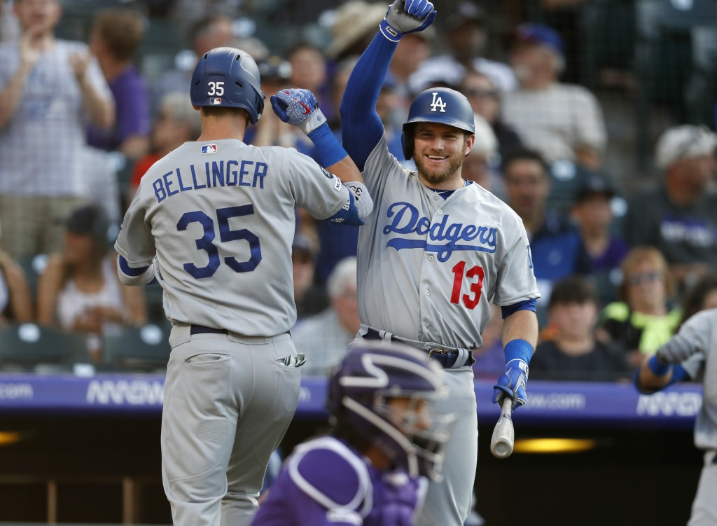 Los Angeles Dodgers' Cody Bellinger, left, is congratulated by Max Muncy after Bellinger's solo home run off Colorado Rockies starting pitcher Peter L...