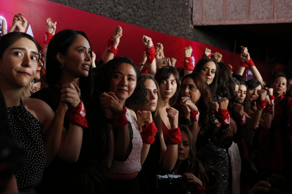 """Women in the Mexican film industry raise their fists wearing red bandanas launching their initiative #YaEsHora or """"The time is now,"""" during the red ca..."""