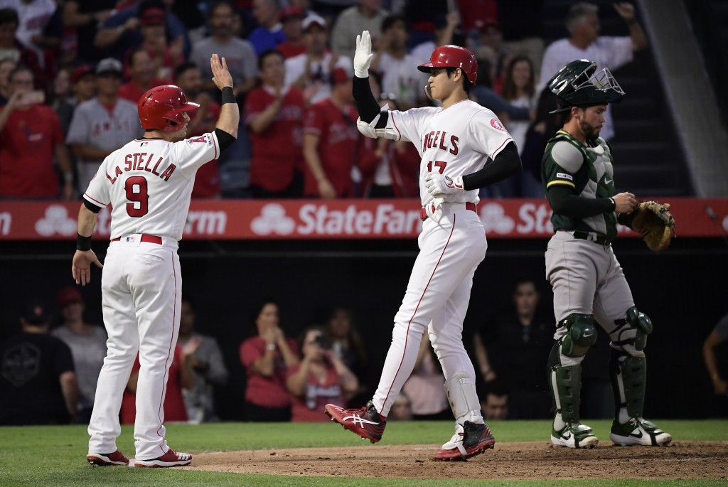 Los Angeles Angels' Shohei Ohtani, center, of Japan, is congratulated by Tommy La Stella, left, after hitting a two-run home run, as Oakland Athletics...