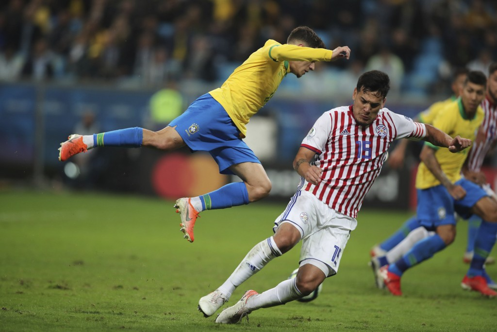 Brazil's Philippe Coutinho, left, falls as he fights for the ball with Paraguay's Gustavo Gomez during a Copa America quarterfinal soccer match at the...