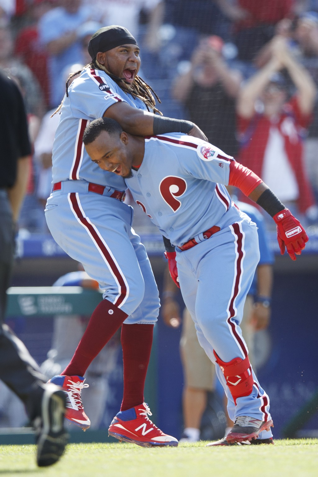Philadelphia Phillies' Jean Segura, right, and Maikel Franco celebrate after Segura hit a game-winning three-run home run off New York Mets relief pit...