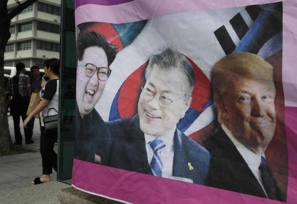 A banner shows images, from left, of North Korean leader Kim Jong Un, South Korean President Moon Jae-in and U.S. President Donald Trump, displayed by...