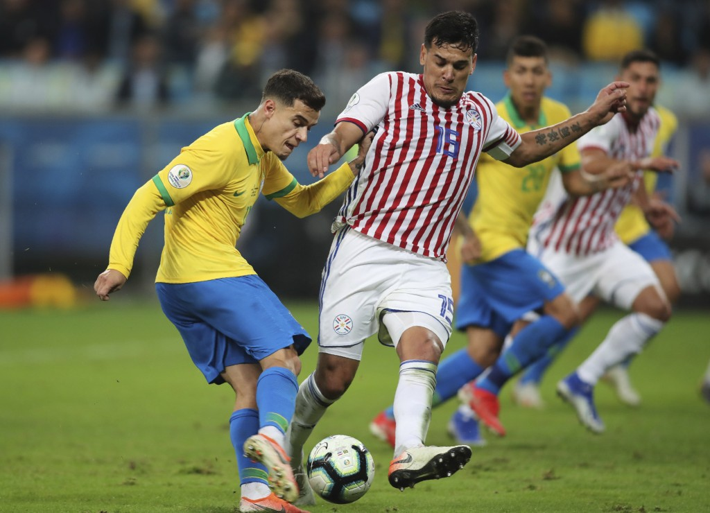 Brazil's Philippe Coutinho strikes the ball challenged by Paraguay's Gustavo Gomez during a Copa America quarterfinal soccer match at the Arena do Gre...