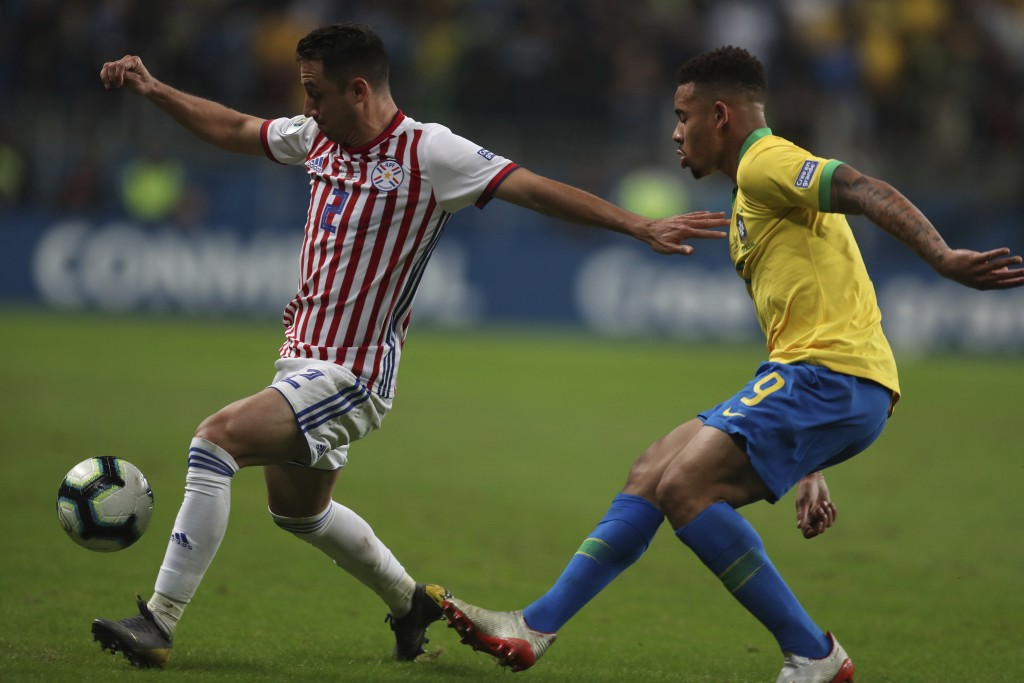Paraguay's Ivan Piris, left, dribbles past Brazil's Gabriel Jesus during a Copa America quarterfinal soccer match at the Arena do Gremio in Porto Aleg...