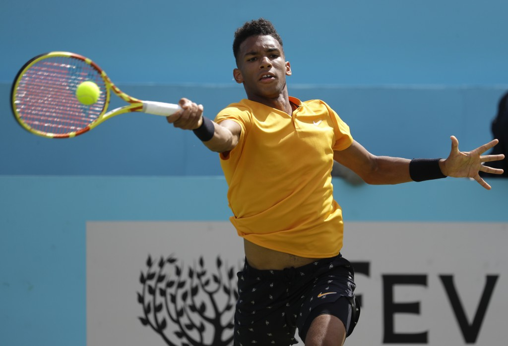 FILE - In this June 21, 2019, file photo, Felix Auger-Aliassime, of Canada, plays a return to Stefanos Tsitsipas, of Greece, during their quarterfinal...