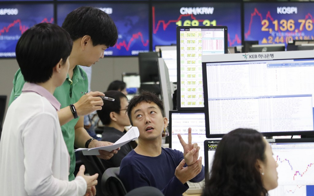 Currency traders work at the foreign exchange dealing room of the KEB Hana Bank headquarters in Seoul, South Korea, Friday, June 28, 2019. Asian stock...