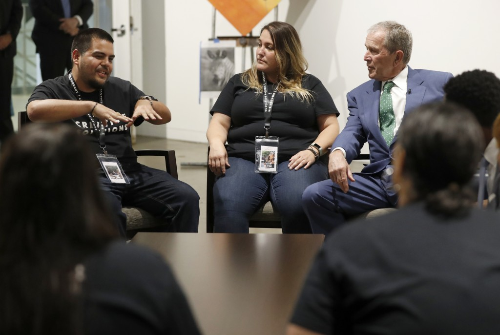 """Big Thought staff members Jose Manuel """"Bone"""" Garcia, left, and Sarah Guerra, center, discuss the non profit youth program with former President George..."""
